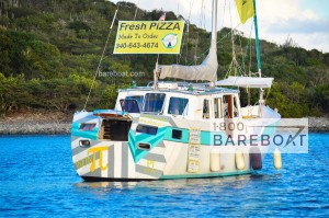 Pizza Pi Sailboat anchored - white sailboat with teal and yellow stripes - mountain behind sailboat